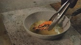 filé : Seafood cooking recipe. Chef turning over shrimp on frying pan with tongs.