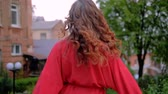 mancha : Female beauty. Relaxed happy woman walking and turning around laughing. Curly ginger red hair.