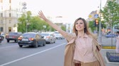 hırslı : Late in big city calling for a cab. Woman flaging taxi standing near road waving her hand Stok Video