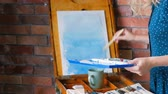 イーゼル : Artist work process. Woman starting new painting on easel. Abstract blue watercolor splotches on paper
