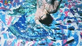 Art devotion. Creative obsession. Relaxed woman smearing paint lying down on colorful backdrop.