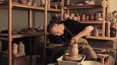 Pottery design. Handmade ceramics. Skilled man shaping clay vase on wheel at studio.