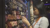 Young Thai Woman choosing scrunchy for hair in accessories store. Slow motion