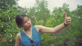 写真の : Young Asian Woman doing selfie in garden