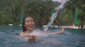 badpak : Thai Girl enjoying her vacation in a swimming pool with water jet. Slow motion