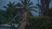 atividades : Young Asian Woman goes into a swimming pool at night. Slow motion
