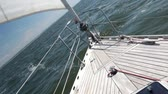 такелаж : View on a wooden deck in the rostrum of yacht. Yacht runs over the waves in bright sunny weather. Staysail is reeled up