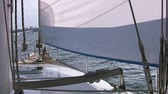 такелаж : Sunny weather. The calm sea. A small ripple on the water. A small sailing boat with sails. View to the yacht bow