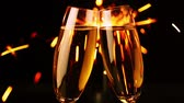 party : Dark background. Two glasses of champagne close-up. Sparks from the burning Bengal light Stock Footage