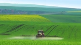 plant fertilizer : Czech Republic. Hilly fields of South Moravia. Tractor watering the young plants of wheat