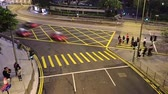 два человека : Hong Kong. Night. Crossroads with pedestrian crossings. Famous two-story trams. Fast motion