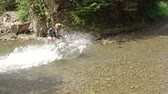 レーサー : Motocross in the wild. The rider crosses the small river. Splashes in the sun. Slow motion 動画素材