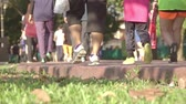 запустить : Summer morning in the park. Sunny weather. Many pedestrians walk along the path. Only feet in focus. Slow motion
