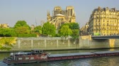 catholic : France. Paris. Sunny summer morning on the Seine embankment. View of Notre Dame in scaffolding after a fire in 2019. Barges pass along the river. Time lapse