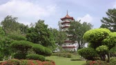 7 : Summer sunny day in a Singapore park. Pagoda among green trees and flower beds. Clouds run fast. Time lapse