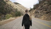 eastern sierra : gimbal shot of teen girl walk on road near merced river
