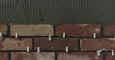 puxar : Slow motion pan of brick cuts tile on the wall Vídeos