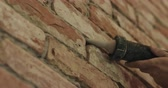 bricklayer : Slow motion handheld closeup of worker filling seam between bricks with mortar from sealant gun