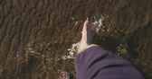 точка зрения : Slow motion pov view man walking barefoot in shallow water on beach