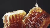 медовый : Slow motion of honey pour over honeycomb on black background