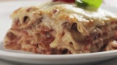 bolognese : Slide shot of homemade lasagna portion on white plate on wood table Stock Footage