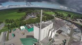 sky : Aerial circling around large industrial factory plant showing the raw materials ready for production and the industrial vehicles piles of sand stone is sunny weather with dark clouds crisp 4k steady