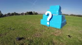 ponto de interrogação : Aerial of white question mark on small bright blue structure drone flying towards cube with? ook showing quadcopter shadow blue sky background footage could indicate FAA drone regulations 4k