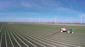crop duster : Aerial view bird flying backwards from tractor spraying chemicals on crops insecticides pesticides field field with young plants ook wind turbines in the background for renewable energy agricultural land Stock Footage