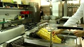 deep fat frying : chef in the action in kitchen french fries in fryer Stock Footage