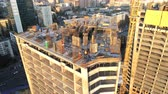scaffolding : Top of high tower building with workers on construction site. Big city development. Metropolis. Aerial view Stock Footage
