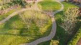 flower bed : Aerial drone view of backyard fruit garden with circle stone path, green grass lawn hills and trees. Landscape design and gardening. Beautiful autumn park landscape Stock Footage
