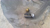 earthmover : Big heavy wheel loader loading sand into dump truck in sand pit. Heavy industrial machinery concept Videos
