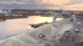 binnenvaartschip : Aerial view of heavy crane loading bulk goods at Dnieper river cargo port terminal in Kiev at evening sunset time. Industrial inland navigation