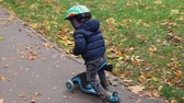 lambreta : Little toddler boy riding scooter balance bike by asphalt walkway together with mother walking near path at city park at autumn outdoors.Small child having fun cycling fast at city street