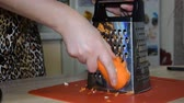 root vegetable dish : Woman rubbing carrots on a grater