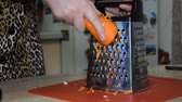 root vegetable dish : Woman rubs carrots on a grater