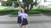 snatch : Cute Asian Thai high schoolgirls student couple in school uniform are having fun playing chasing and catching a doll with her student friend with action camera moving Stock Footage