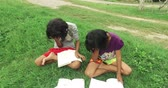 Funny Asian Thai girl children couple is bored with difficult books and homework and lie down sleeping with book cover their faces. Lazy kindergarten girls quit study in kid education concept in HD