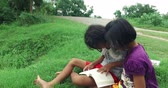 Cute Asian Thai girl children couple in casual clothes reading book and study in green field rural nature environment and find something exciting together. Happy young kindergarten or elementary schoolgirls learning in kid education concept in 4k Stock Footage