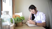 Cute Asian Thai high school girl in uniform studying and thinking of difficult exam on desk in private room with plants and window decoration in schoolgirl fashion and education concept HD