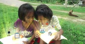 Poor Asian Thai girl children couple in casual clothes reading book studying in green field rural nature environment and discover something exciting together with magical animation icon flying from books. Happy kindergarten schoolgirls kids internet learn