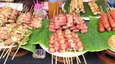 quibe : Slow motion of skewer pork sausage and ham barbecue in native open market of Thailand. Charcoal grill meat sausage and ham roll with vegetable and golden needle mushroom on a stick native Thai cuisine food with camera movement in 4k.