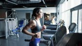 studnia : Young woman using a treadmill in health club Wideo