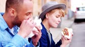 consumidor : Couple sitting at curb and eating hamburgers
