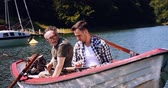 pesca : Two generation men sitting in rowboat
