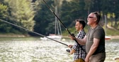 pesca : Son with father fishing at sunny day Stock Footage