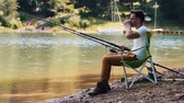 captura : Man sitting on fishing chair and fishing Stock Footage