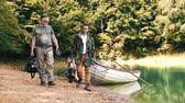 Male friends walking with fishing tackle