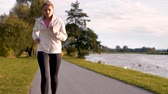 Female athlete running along a road Stock Footage