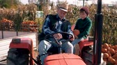 Grandfather explaining to boy how to drive a tractor Stock Footage